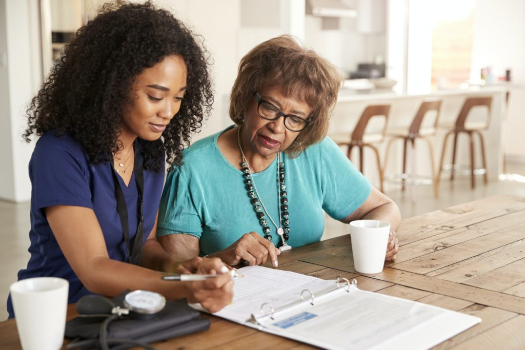 Female healthcare worker filling in a form with a senior woman during a home health visit