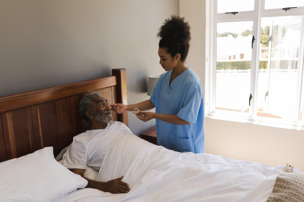 Woman doctor fitting a senior man with hearing aid in bed